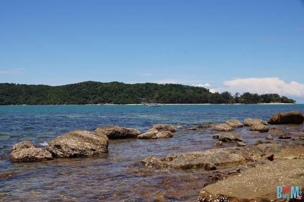 Steinstrand der Insel Mamutik. Ausblick auf die Nachbarinsel Manukan. Beide Teil des Tunku Abdul Rahman Nationalparks