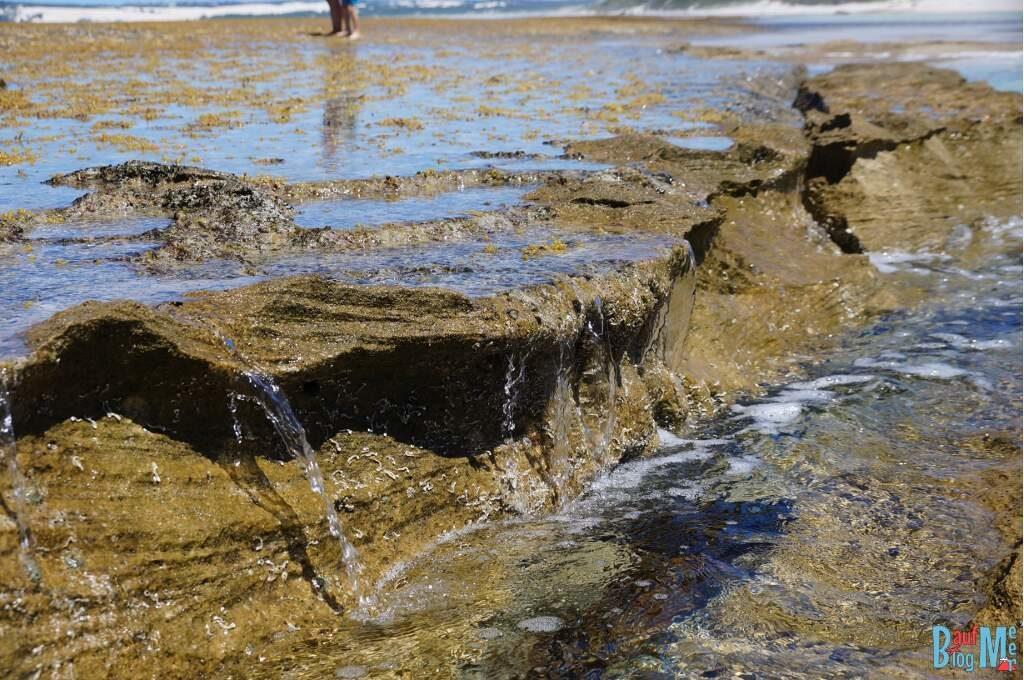 Felsen trennen den Strand vom Meer, so dass man sicher vor der Brandung baden kann